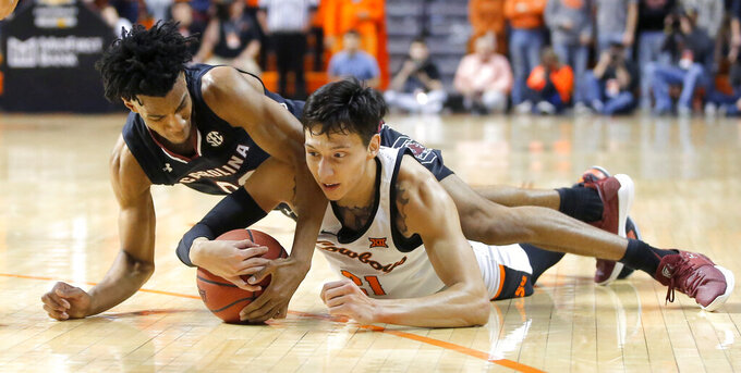 Oklahoma State's Lindy Waters III (21) and A.J. Lawson (00) fight for control of the ball during an NCAA college basketball game in Stillwater, Okla., Saturday, Jan. 26, 2019.(Bryan Terry/The Oklahoman via AP)