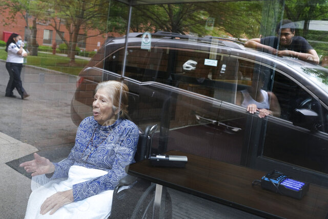 Gloria DeSoto, 92, bottom left, visits with her family, reflected in the glass in their car, from a window of the Hebrew Home at Riverdale, where she lives, in New York, Thursday, June 11, 2020. Her family was able to visit by a speaker while they stayed in their car and DeSoto stayed behind the glass of an entryway. They had not been able to visit since March 10, when many nursing homes began to shut down visitations for fear of spreading the coronavirus. The Hebrew Home at Riverdale, home to 700 residents, just started these non-contact visitations and will be scheduling them seven days a week to help families and residents reconnect. (AP Photo/Seth Wenig)