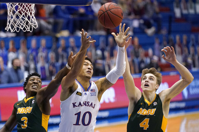Kansas' Jalen Wilson (10) beats North Dakota State's Tyree Eady (3) and Grant Nelson (4) to a rebound during the second half of an NCAA college basketball game Saturday, Dec. 5, 2020, in Lawrence, Kan. (AP Photo/Charlie Riedel)