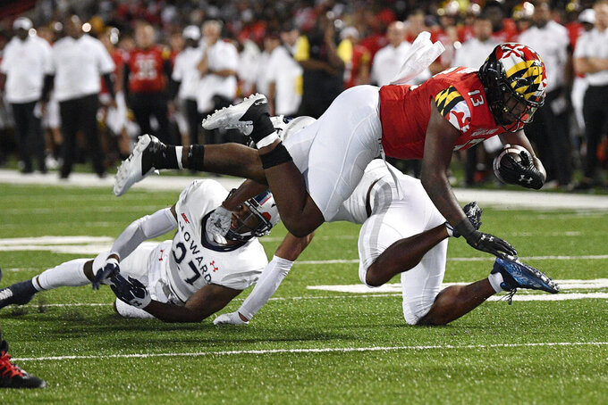 Maryland running back Peny Boone (13) carries the ball past Howard defensive back Aaron Walker (27) during the first half of an NCAA college football game, Saturday, Sept. 11, 2021, in College Park, Md. (AP Photo/Nick Wass)