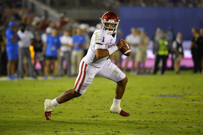 FILE - In this Sept. 14, 2019, file photo, Oklahoma quarterback Jalen Hurts runs the ball during the second half of an NCAA college football game against UCLA in Pasadena, Calif. While Oklahoma appears to have another serious Heisman contender with Big 12 newcomer and dual-threat graduate transfer Jalen Hurts, the Longhorns have one of the eight underclassmen starting quarterbacks in the league. Texas junior Sam Ehlinger is off to a record-setting pace that could also get him in that Heisman conversation.(AP Photo/Mark J. Terrill, File)