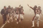 FILE - In this Dec. 31, 1988, file photo, Chicago Bears free safety Maurice Douglass (37) runs out of the fog and is congratulated by teammates after intercepting a Philadelphia Eagles pass late in the fourth quarter of an NFL football playoff game in Chicago. Chicago's victory in the Fog Bowl 30 years ago is the only time the Bears have defeated the Eagles in three playoff meetings. The Bears get another chance when they host the Eagles in an NFC wild-card game. (AP Photo/Mark Elias, File)