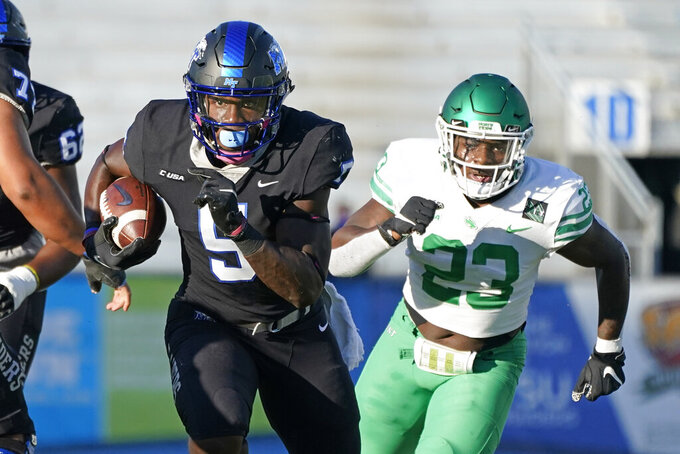 Middle Tennessee running back Chaton Mobley (5) carries the ball ahead of North Texas linebacker KD Davis (23) in the first half of an NCAA college football game Saturday, Oct. 17, 2020, in Murfreesboro, Tenn. (AP Photo/Mark Humphrey)