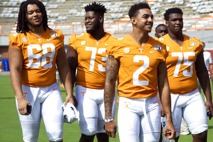 Tennessee quarterback Jarrett Guarantano (2), center, along with, from left, offensive linemen Marcus Tatum (68), Trey Smith (73), and Jerome Carvin (75) walk along the field during Tennessee's NCAA college football Fan Day and team photo shoot in Knoxville, Tenn. Sunday, Aug. 4, 2019. (Saul Young/Knoxville News Sentinel via AP)