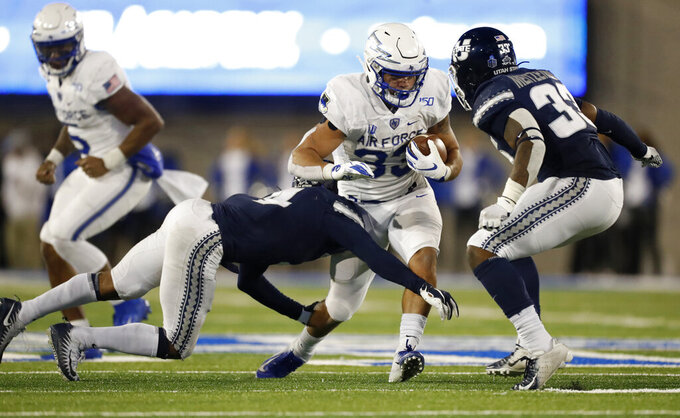 FILE--In this Oct. 26, 2019, file photo, Air Force fullback Taven Birdow, center, is stopped by Utah State safety Shaq Bond, left, and linebacker Kevin Meitzenheimer during the second half of an NCAA college football game at Air Force Academy, Colo. Birdow's father, Jermaine, saw for the first time his son play football when Air Force hosted Army on Saturday, Nov. 2. (AP Photo/David Zalubowski, File)