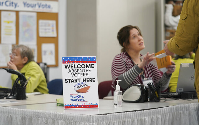 FILE - In this Jan. 17, 2020, file photo, a poll worker speaks with a voter as Minneapolis Early Voting Center opened, in Minneapolis. Early voting in the crush of Super Tuesday states that hold primaries on March 3 amounts to a parallel campaign for the Democratic nomination. While much of the focus is on who will come out on top in the traditional first four voting states, early voting will allow a much broader swath of voters to play a key role in picking the nominee. In Minnesota, in-person early voting began Jan. 17. Vermont's deadline to mail out its absentee ballots was the same day. Many of the 14 Super Tuesday states will offer some form of early voting between now and mid-February. (Glen Stubbe/Star Tribune via AP, File)