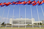 FILE - In this April 9, 2020, file photo, North Korean flags flutter in front of the Presidium of the Supreme People's Assembly building in Pyongyang, North Korea. North Korea will convene its rubber-stamp parliament on Sept. 28, 2021 to discuss efforts to salvage an economy strained by pandemic border closures after decades of mismanagement and U.S.-led sanctions. (Kyodo News via AP, File)