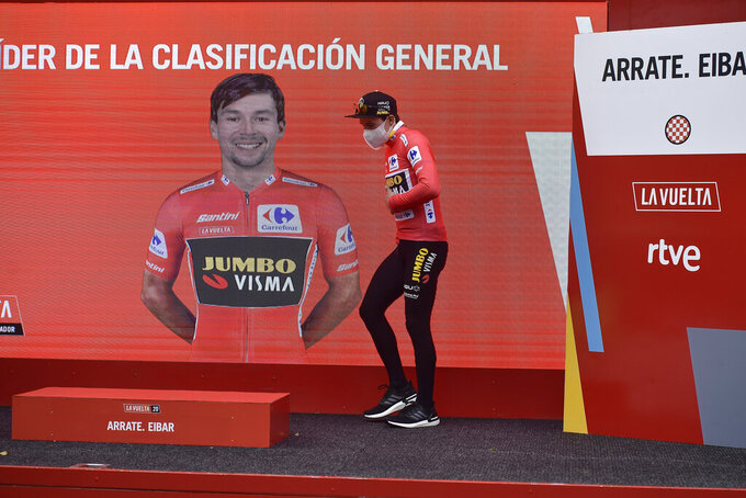 Jumbo-Visma's Primoz Roglic, with the read shirt as leader of the race, approaches the podium after winning the first stage of La Vuelta between Irun and Arrate, in northern Spain, Tuesday, Oct. 20, 2020.  Defending champion Roglic attacked in the final kilometer after a difficult climb to win the opening stage of the Spanish Vuelta. (AP Photo/Alvaro Barrientos)