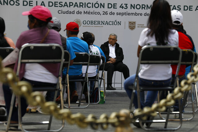 Mexico's President Andres Manuel Lopez Obrador, center, and family members of 43 missing students from the Rural Normal School of Ayotzinapa, listen to an update to the ongoing investigations on the sixth anniversary of the students' disappearance, at the National Palace in Mexico City, Saturday, Sept. 26, 2020. (AP Photo/Rebecca Blackwell)
