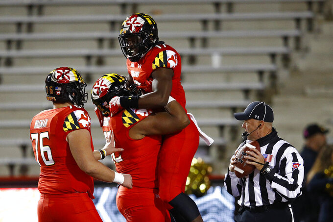 Maryland tight end Chigoziem Okonkwo, top center, celebrates his touchdown with teammates Evan Gregory (52) and Jack Wagman in the second half of an NCAA college football game, Saturday, Oct. 27, 2018, in College Park, Md. (AP Photo/Patrick Semansky)