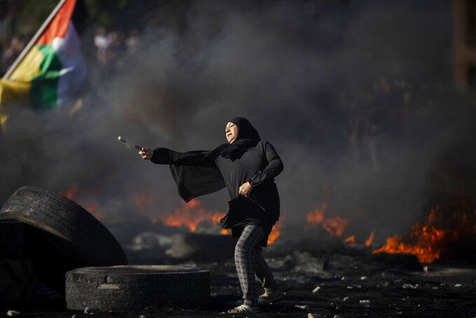 Palestinians clash with Israeli forces at the Hawara checkpoint, south of the West Bank city of Nablus, Tuesday, May 18, 2021. (AP Photo/Majdi Mohammed)