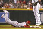 Los Angeles Angels' Shohei Ohtani dives back into second base under Arizona Diamondbacks shortstop Nick Ahmed during the seventh inning of a baseball game Friday, June 11, 2021, in Phoenix. (AP Photo/Rick Scuteri)