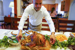 Esdras Zayas places the Thanksgiving turkey on the dining room table before his family celebrates their first holiday without their beloved mother Ana Martinez who died at 78 on April 1 while recovering at a nursing home from a knee replacement, Thursday, Nov. 26, 2020, in Deer Park, N.Y. (AP Photo/John Minchillo)