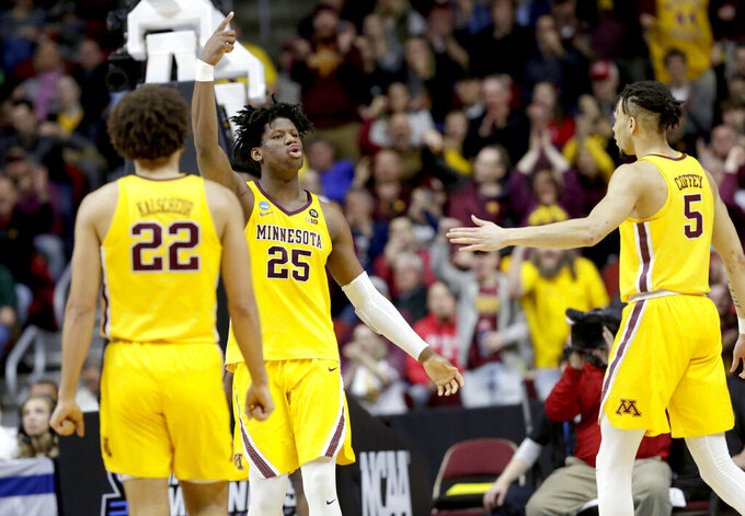 Minnesota's Daniel Oturu (25) reacts next to teammates Gabe Kalscheur (22) and Amir Coffey (5) after a basket and a foul during the first half of a first round men's college basketball game against Louisville in the NCAA Tournament, in Des Moines, Iowa, Thursday, March 21, 2019. (AP Photo/Nati Harnik)