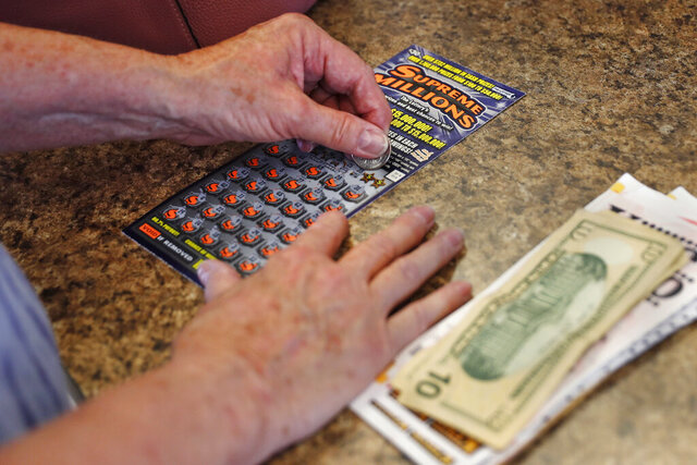 A woman scratches a $30 instant ticket while playing the lottery at Ted's Stateline Mobil on Wednesday, June 24, 2020 in Methuen, Mass. The coronavirus pandemic has been a rollercoaster for state lotteries across the country, with some getting a boost from the economic downturn and others scrambling to make up for revenue shortfalls. (AP Photo/Charles Krupa)