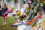 FILE - In this March 17, 2019, file photo, a girl carries flowers to a memorial wall following the mosque shootings in Christchurch, New Zealand. New Zealand's parliament on Wednesday passed sweeping gun laws which outlaw military-style weapons, less than a month after the nation's worst mass shooting left 50 dead and 39 wounded in two mosques in the South Island city of Christchurch. (AP Photo/Vincent Thian, File)