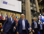 European Council President Donald Tusk, left, and European Commission President Jean-Claude Juncker, center, make their way to a media conference at an EU summit in Brussels, Thursday, March 21, 2019. Worn down by three years of indecision in London, EU leaders on Thursday were grudgingly leaning toward giving the U.K. more time to ease itself out of the bloc. (AP Photo/Virginia Mayo)