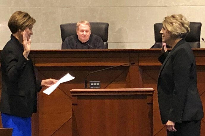Iowa Gov. Kim Reynolds, left, issues the oath of office to Judge Julie Schumacher, the governor's latest appointment to the Iowa Court of Appeals, as Chief Judge Thomas Bower looks on Thursday, Oct. 17, 2019 at Iowa Judicial Branch Building in Des Moines, Iowa.(AP Photo/David Pitt)
