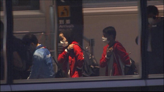 In this image made from a video, Afghan athletes Zakia Khudadadi, center left, and Hossain Rasouli, center right, arrive at Haneda airport in Tokyo Saturday, Aug. 28, 2021. They have arrived in Tokyo, via what's been described as a harrowing journey from Kabul to Paris, to compete in the Paralympics. (TBS via AP)