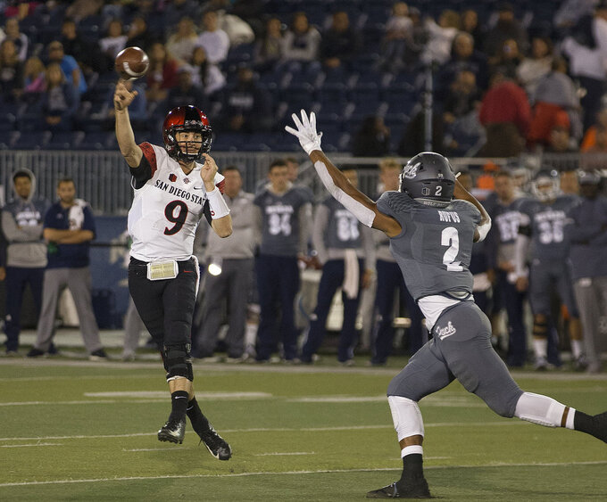 San Diego State quarterback Ryan Agnew (9) throws over Nevada's Asauni Rufus (2) in the first half of an NCAA college football game in Reno, Nev., Saturday, Oct. 27, 2018. (AP Photo/Tom R. Smedes)