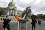 Local political activist Gene Stilp, right, pulls down a cut-out of President Donald Trump while staging an anti-Trump demonstration in front of the Pennsylvania State Capitol, Sunday Jan. 17, 2021, in Harrisburg, Pa. (AP Photo/Jacqueline Larma)