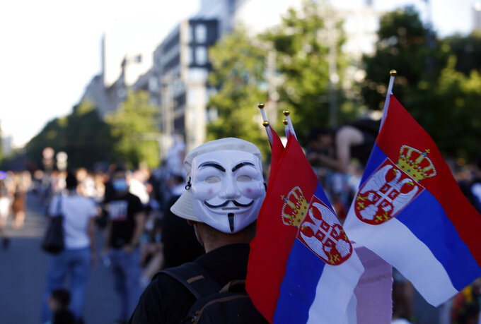 A street vendor holds Serbian flags during a protest in front Serbian Parliament building in Belgrade, Serbia, Thursday, July 9, 2020. Serbia's authorities on Thursday banned gatherings of more than 10 people in the capital Belgrade after two nights of violent clashes between police and thousands of demonstrators protesting coronavirus lockdown measures. (AP Photo/Darko Vojinovic)