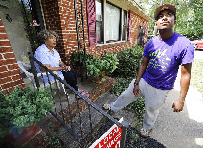 FILE - In this Saturday, Sept. 10, 2016 file photo, Rodney Smith Jr., founder of Raising Men Lawn Care Service, looks skyward while talking with homeowner Irene Renee Jolly in Huntsville, Ala. Inspired to provide free lawn care several years ago, Smith said he has now completed a quest to provide free lawn care for veterans in every U.S. state, Friday, June 14, 2019. (AP Photo/Jay Reeves, File)