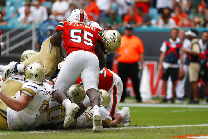 Georgia Tech running back Jordan Mason, top rear, goes over the top to score against Miami linebacker Shaquille Quarterman (55) during an overtime period of an NCAA college football game, Saturday, Oct. 19, 2019, in Miami Gardens, Fla. Georgia Tech defeated Miami 28-21 in overtime. (AP Photo/Wilfredo Lee)