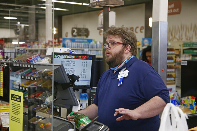 Cashier Trent Cagle stand behind a plexiglass shield as he scan items at a Homeland grocery store Friday, March 27, 2020, in Oklahoma City. Homeland and other stores have installed the shields due to concerns over the COVID-19 virus. (AP Photo/Sue Ogrocki)