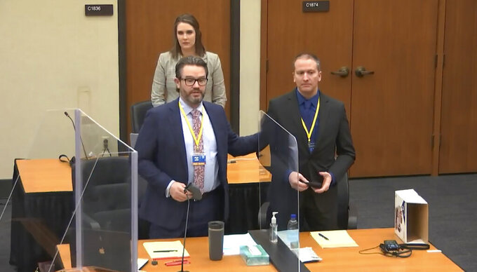 In this screen grab from video, defense attorney Eric Nelson, left, defendant and former Minneapolis police officer Derek Chauvin, right, and Nelson's assistant Amy Voss, back, introduce themselves to potential jurors as Hennepin County Judge PeterCahill Tuesday, March 23, 2021, presides over jury selection in the trial of Chauvin at the Hennepin County Courthouse in Minneapolis, Minn.   Chauvin is charged in the May 25, 2020 death of George Floyd.  (Court TV, via AP, Pool)