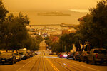 Under darkened skies from wildfire smoke, a man crosses Hyde Street with Alcatraz Island and Fisherman's Wharf in the background Wednesday, Sept. 9, 2020, in San Francisco. People from San Francisco to Seattle woke Wednesday to hazy clouds of smoke lingering in the air, darkening the sky to an eerie orange glow that kept street lights illuminated into midday, all thanks to dozens of wildfires throughout the West. The picture was taken in the middle of the day at 12:29 p.m. (AP Photo/Eric Risberg)