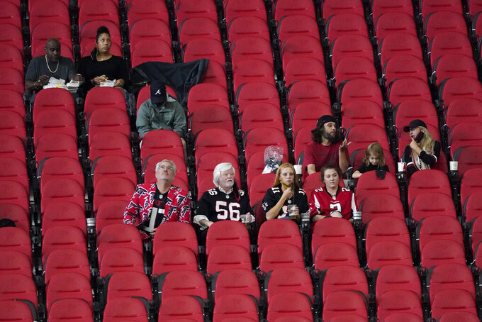 Fans watch during the first half of an NFL football game between the Atlanta Falcons and the Carolina Panthers, Sunday, Oct. 11, 2020, in Atlanta. This is the first game with fans allowed in the stands at Mercedes-Benz Stadium. (AP Photo/John Bazemore)