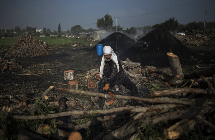 A Palestinian man cuts wood using a chainsaw in a traditional charcoal production site in the town of Jabaliya, Northern Gaza Strip, Thursday, Jan. 7, 2021.(AP Photo/Khalil Hamra)