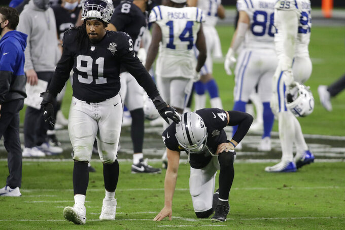 Las Vegas Raiders defensive tackle Kendal Vickers (91) comforts quarterback Derek Carr (4) after a loss to the Indianapolis Colts in an NFL football game, Sunday, Dec. 13, 2020, in Las Vegas. (AP Photo/Isaac Brekken)