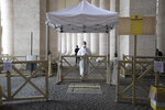 Medical personnel wait for visitors to check their temperatures to prevent the spread of COVID-19 in a control point set under the colonnade designed by 16th century Italian sculptor and architect Gian Lorenzo Bernini, St. Peter's square at the Vatican in the day of the reopening of St. Peter's Basilica, Monday, May 18, 2020. Italy is slowly lifting sanitary restrictions after a two-month coronavirus lockdown. (AP Photo/Alessandra Tarantino)