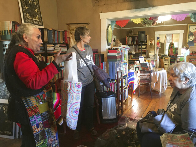 A Thursday December 26, 2019 photo shows author Denise Chavez at her Casa Camino Real bookstore in Las Cruces with Border Servant Corps volunteers. The nonprofit group helps deliver books to migrant families in Ciudad Juárez as part of the