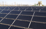 FILE - In April 20, 2011, file photo, rows of solar panels that make up Public Service Company of New Mexico's new 2-megawatt photovoltaic array sit in front of the utility's natural gas-fired generating station in Albuquerque, N.M. The parent company of New Mexico's largest electric utility will become part of energy giant Iberdrola's global holdings under a multibillion-dollar merger.  Under the agreement announced Wednesday, Oct. 21, 2020, Iberdrola's majority-owned U.S. subsidiary Avangrid will acquire PNM Resources and its assets in New Mexico and Texas. The merger will require approval from a number of state and federal regulators in a process that's expected to take the next 12 months. (AP Photo/Susan Montoya Bryan, File)