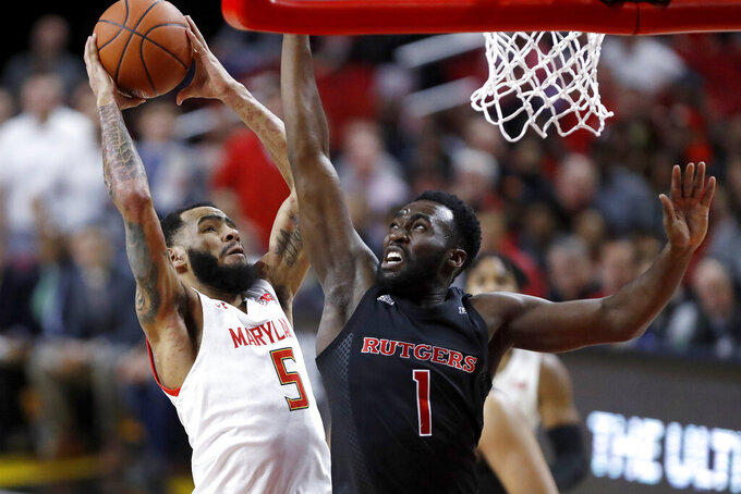 Maryland guard Eric Ayala (5) goes up for a shot against Rutgers forward Akwasi Yeboah (1) during the first half of an NCAA college basketball game Tuesday, Feb. 4, 2020, in College Park, Md. (AP Photo/Julio Cortez)