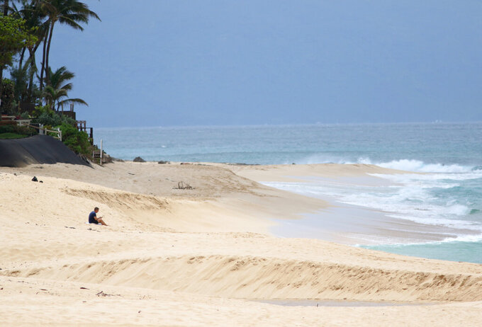 A man sits alone on Oahu's North Shore near Haleiwa, Hawaii, Tuesday, March 31, 2020. The state of Hawaii is reporting its first death of an individual who tested positive for the coronavirus. The state Department of Health says the individual was an older male resident of Oahu. He had been hospitalized recently with multiple medical issues but it's not clear what his cause of death was. He did test positive for the disease and had been exposed to someone who had tested positive. (AP Photo/Caleb Jones)