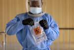 Divine Ayong seals a test in a biohazard bag after collecting a sample Monday, Sept. 21, 2020, at The University of Texas at El Paso's Fox Fine Arts building in El Paso, Texas. Deaths per day from the coronavirus in the U.S. are on the rise again, just as health experts had feared, and cases are climbing in nearly every single state. In El Paso, authorities instructed people to stay home for two weeks and imposed a 10-p.m.-to-5-a.m. curfew because of a surge that has overwhelmed hospitals. (Mark Lambie/The El Paso Times via AP)
