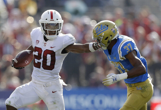 Stanford running back Bryce Love (20) stiff-arms UCLA defensive back Quentin Lake (37) during the first half of an NCAA college football game Saturday, Nov. 24, 2018, in Pasadena, Calif. (AP Photo/Marcio Jose Sanchez)