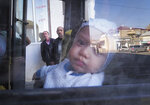 A street is reflected in a window as a baby sitting on his mother prepare to leave Stepanakert, the separatist region of Nagorno-Karabakh, Friday, Oct. 30, 2020. The Azerbaijani army has closed in on a key town in the separatist territory of Nagorno-Karabakh following more than a month of intense fighting. (AP Photo)