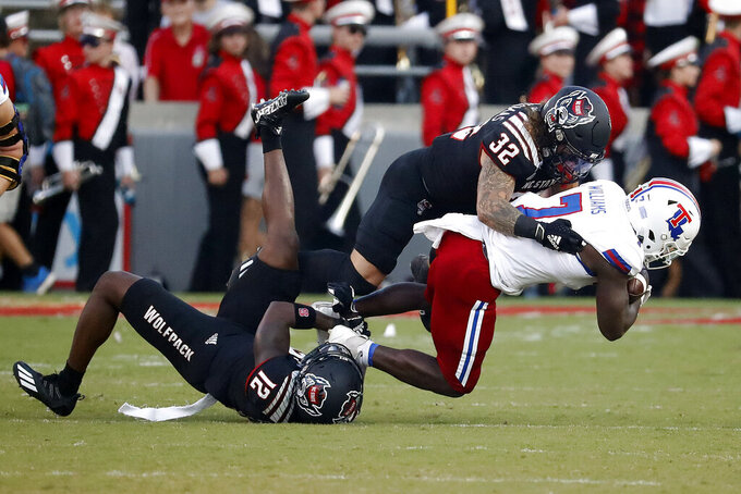 North Carolina State's Drake Thomas (32) and Devan Boykin (12) combine to take down Louisiana Tech's Marcus Williams Jr. (7) during the first half of an NCAA college football game in Raleigh, N.C., Saturday, Oct. 2, 2021. (AP Photo/Karl B DeBlaker)