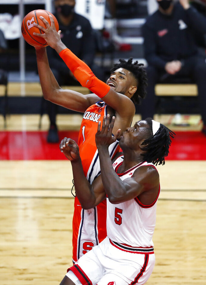 Syracuse forward Quincy Guerrier (1) goes to the basket against Rutgers center Cliff Omoruyi (5) during the first half of an NCAA college basketball game in Piscataway, N.J., Tuesday, Dec. 8, 2020. (AP Photo/Noah K. Murray)
