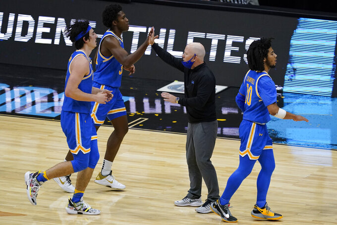 UCLA head coach Mick Cronin, center, celebrates with his team during the second half of a men's Final Four NCAA college basketball tournament semifinal game against Gonzaga, Saturday, April 3, 2021, at Lucas Oil Stadium in Indianapolis. (AP Photo/Darron Cummings)