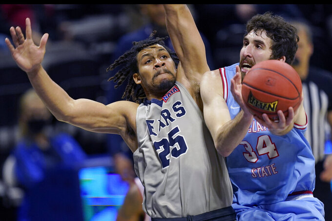Lewis-Clark State forward Jake Albright (34) shoots while covered by Shawnee State forward Latavious Mitchell (25) during the first half of an NAIA basketball game in the finals of the national tournament in Kansas City, Mo., Tuesday, March 23, 2021. (AP Photo/Orlin Wagner)