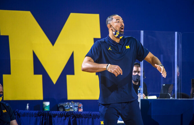 Michigan head coach Juwan Howard shouts to his players from courtside in the first half of an NCAA college basketball game against Northwestern at Crisler Center in Ann Arbor, Mich., Sunday, Jan. 3, 2021. (AP Photo/Tony Ding)