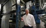 In this Tuesday, Aug. 6, 2019, photo, Mark Brown poses for a photo standing next to the presses as they run The Vindicator newspaper in Youngstown, Ohio. The Youngstown paper announced in June it would cease publication Saturday, Aug. 31, because of financial struggles, but the paper will be printed by the Tribune Chronicle, which has bought The Vindicator name, subscriber list and website from owners of the Youngstown publication. (AP Photo/Tony Dejak)