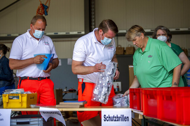 Mobile teams testing people on the coronavirus collect their equipment at a fire station in Rheda-Wiedenbrueck, Germany, Monday, June 23, 2020. The mobile teams from the German Federal Armed Forces and aid organizations are formed to visit and test people in quarantine throughout the Guetersloh region. (David Inderlied/dpa via AP)