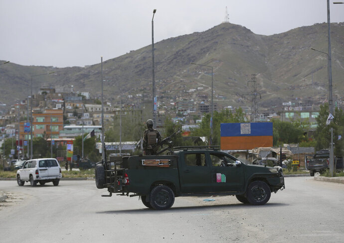 Afghan security forces inspect the site of a bomb explosion in Kabul, Afghanistan, Monday, May 18, 2020. A suicide bomber in a stolen military Humvee targeted a base in eastern Afghanistan belonging to the country's intelligence service early on Monday, killing many members of the force. The Taliban claimed responsibility for the attack. (AP Photo/Rahmat Gul)